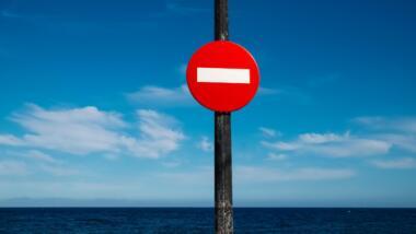"""Bild mit Himmel und ein bisschen Meer, davor ein """"Durchfahrt verboten""""-Schild."""