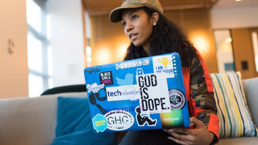 Frau sitzt hinter Laptop, der mit Stickern beklebt ist