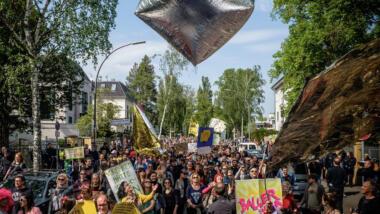 Demonstration. Über der Demo fliegt ein großer aufgeblasener Stein.