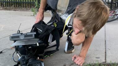 Ein Kameramann des Denver Channel schaut sich seine Kamera an, nachdem er mit Paintballs und Tränengas beschossen wurde.