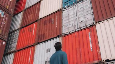 Mann steht vor aufragender Wand aus Schiffscontainern und schaut nach oben.