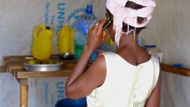 Frau in UNHCR-Camp mit Telefon
