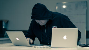 Mann im Kapuzenpulli an Laptops