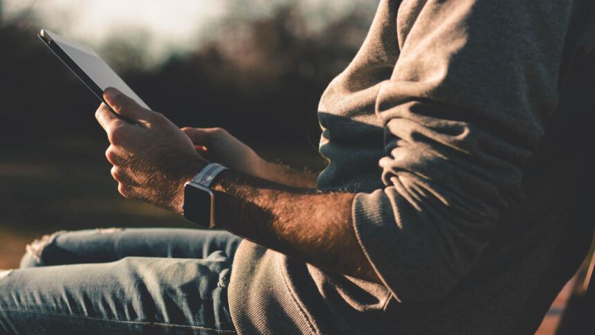 Mann liest auf IPad