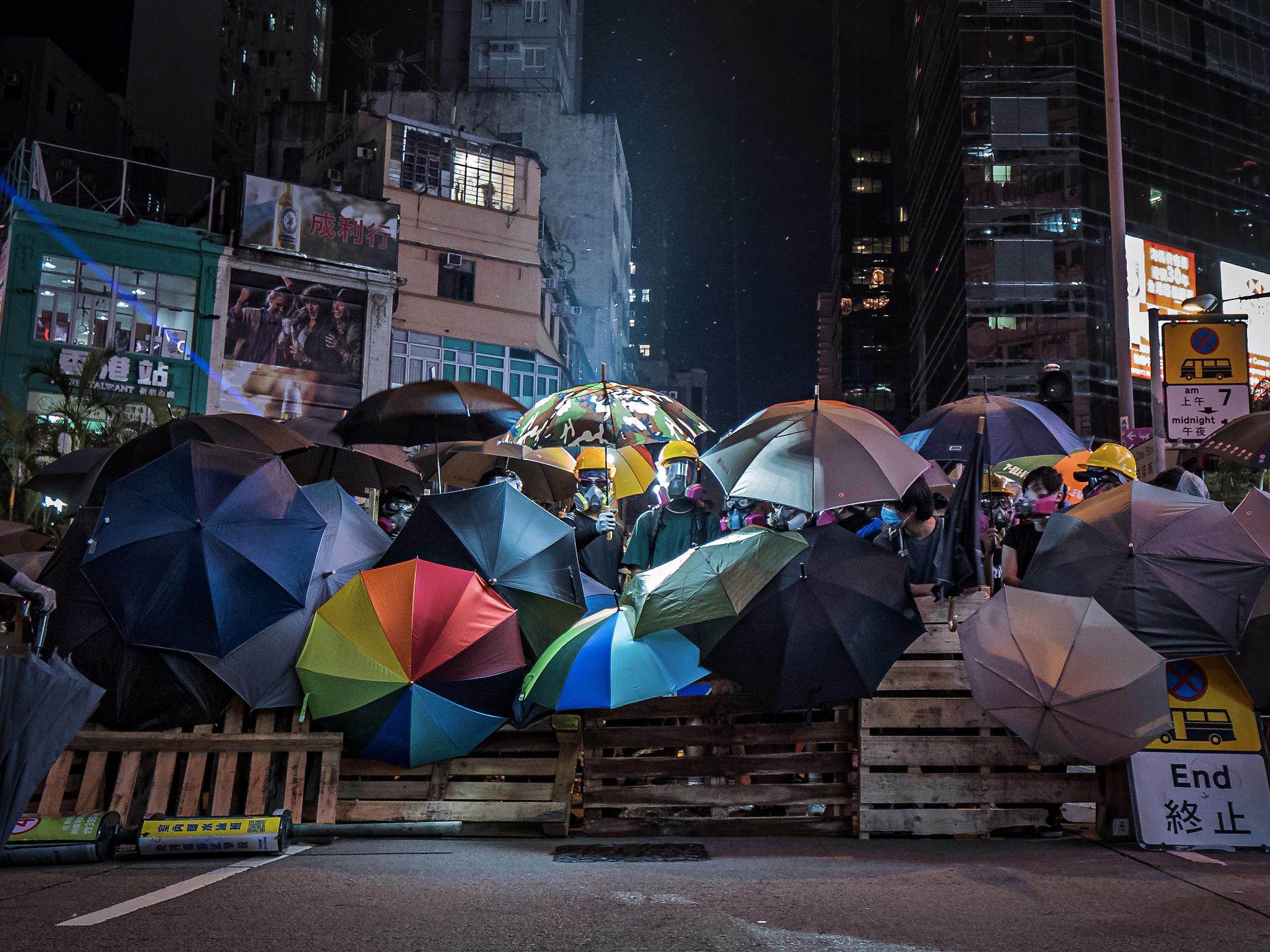 Menschen mit Regenschirmen an einer Barrikade