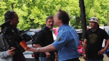 Am Oberarm das Wappen des Landes Berlin, die Hand an der Kamera des ZDF-Fernsehteams.