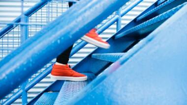 Blaue Treppe mit Füßen in roten Schuhen, die nach oben gehen.
