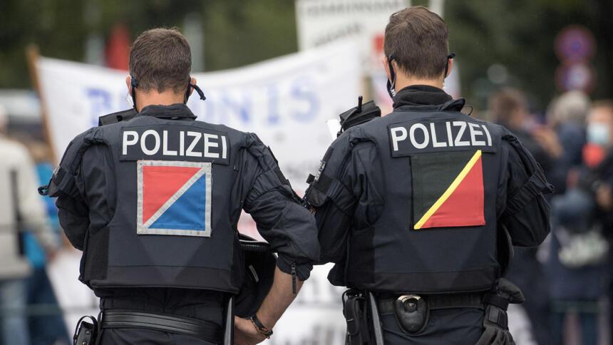 Zwei Polizisten stehen vor einer Demo