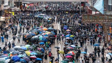 Demonstrant:innen sammeln sich mit Regenschirmen in Hongkongs Straßen.