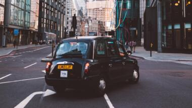 """Taxi vor Londoner Kulisse mit """"Gurke"""" im Hintergrund"""