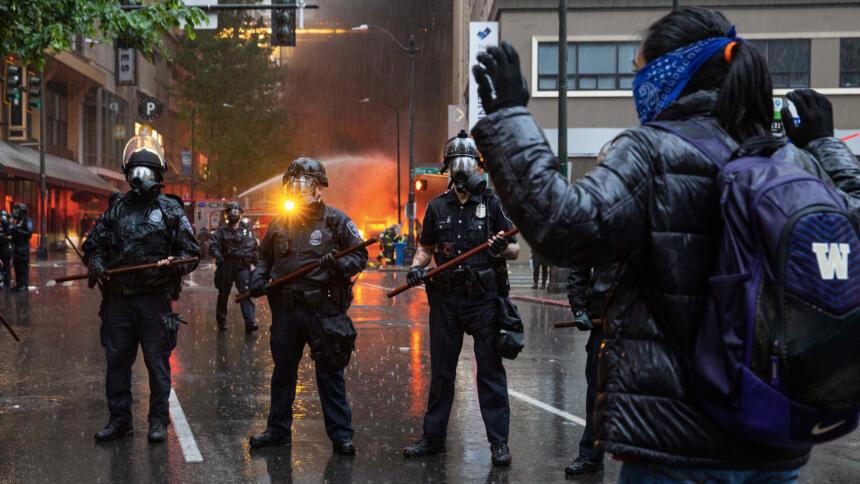 Frau steht mit erhobenen Armen vor einer Polizeikette, hinten löscht ein Feuerwehrfahrzeug einen Brand