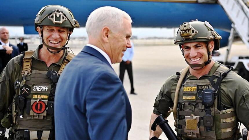 Mike Pence in blauem Jacket zwischen zwei Polizisten mit Helmen und schusssicheren Westen