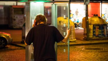 Mann telefoniert in Telefonzelle