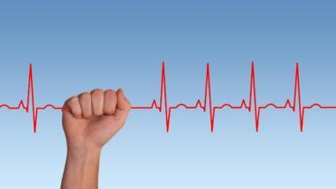 Eine Hand greift nach einer EKG-Kurve.