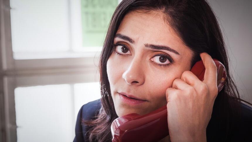 Frau mit Telefonhörer in der Hand