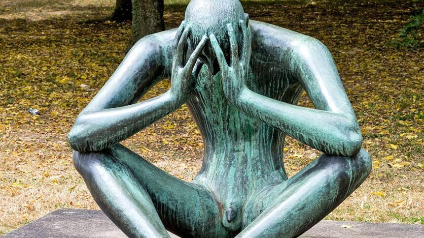 """Skulptur """"Der Denker"""": Eine Person sitzt auf dem Boden und hat das Gesicht in den Händen verborgen."""