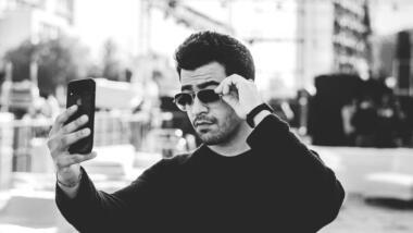 Mann mit Sonnenbrille fotografiert sich mit handy