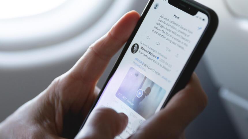Mensch hält Smartphone in der Hand, auf dem Twitter zu sehen ist