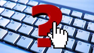 Ein altmodischer Mauszeiger klickt ein rotes Fragenzeichen an, im Hintergrund eine Tastatur.