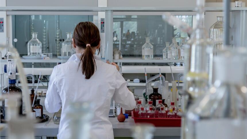 Frau steht im Labor umgeben von Kolben, Reagenzgläsern und anderen Gerätschaften.