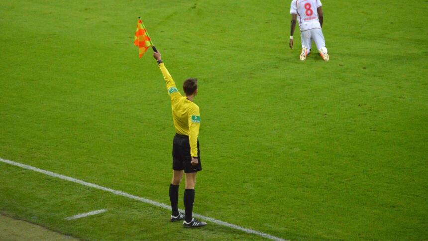 Ein Linienrichter an der Seitenlinie hebt die Fahne.