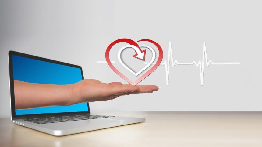 Eine Hand kommt aus einem Laptop-Bildschirm und transportiert ein gezeichnetes Herz und eine Herzschlag-Kurve.