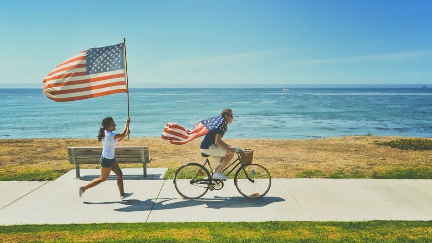 Kinder fahren und laufen am Strand mit US-Flaggen