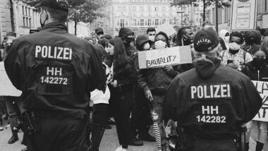 Polizist:innen stehen von einer Demonstration