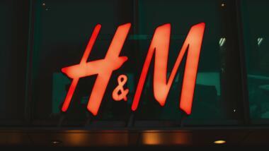 Das H&M Logo leuchtet an einem dunklen Gebäude
