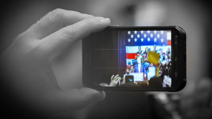 Ein Smartphone filmt Donald Trump vor einer großen US-Flagge