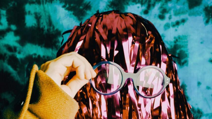 Person mit Lametta-Haaren setzt sich nerdige Brille auf