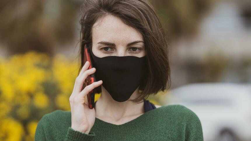 Ein Mensch telefoniert am Handy mit Maske
