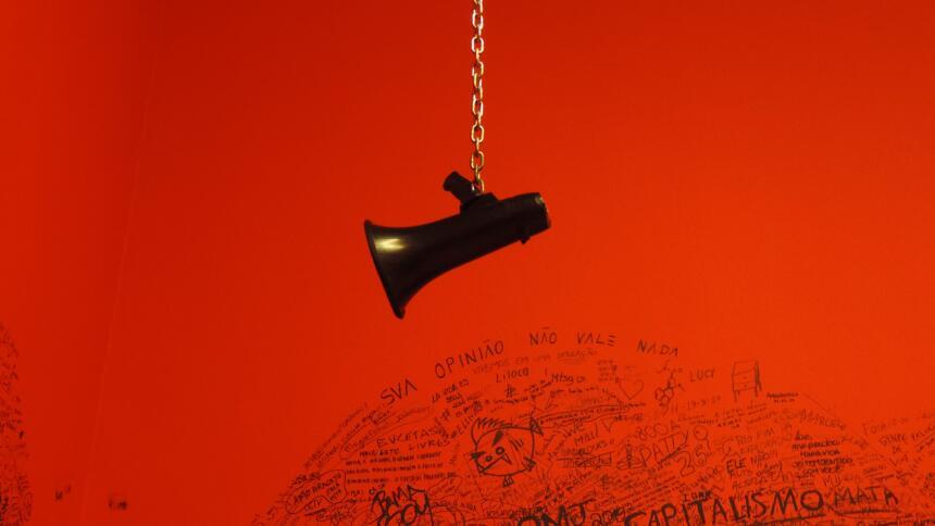 Symbolbild Megafon vor rotem Hintergrund