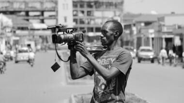 Ein Mann hält eine Kamera, schwarz-weiß-Fotografie