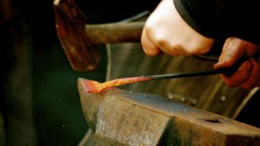 Jemand haut mit einem Hammer auf ein glühendes Stück Metall, um es zu schmieden
