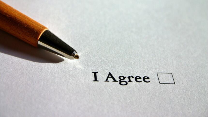 """Ein Stift liegt auf einem Blatt Papier mit einem Kästchen, neben dem """"I Agree"""" steht."""