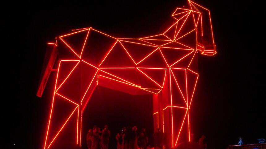 Ei aus Dreiecken zusammengesetzte, rot beleuchtete Pferdefigur