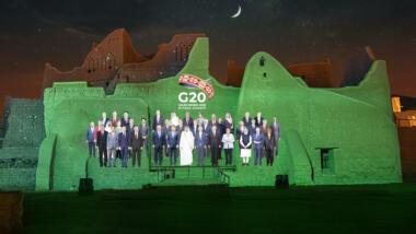 Die Vertreter:innen der G20 Mitgliedsstaaten in einem virtuellen Gruppenfoto auf eine Wand projiziert.
