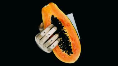Eine Roboterhand greift in eine halbierte Papaya