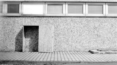 Eine Hintertür, die auf eine Betonwand stößt, schwarz-weiß-Bild