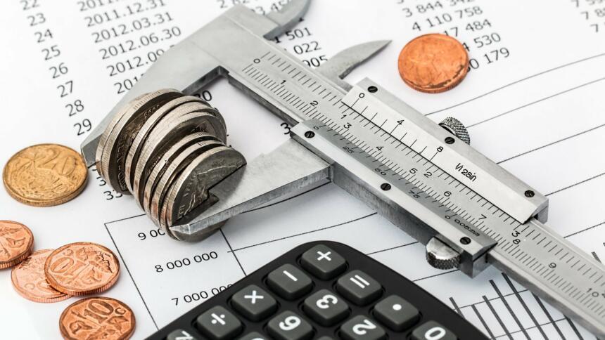 Ein Taschenrechner und Geld auf einem Kontobuch.