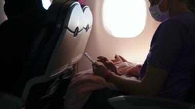 Person mit Maske sitzt in Flugzeug und tippt auf dem Smartphone