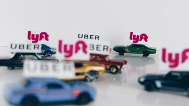 Spielzeugautos mit kleinen Flaggen der Logos von Lyft und Uber.