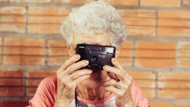 Eine Frau mit grauen Haaren schaut durch den Sucher einer Kamera.