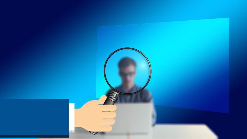 Eine Lupe zeigt eine verschwommene Figur, die vor einem Computer sitzt.