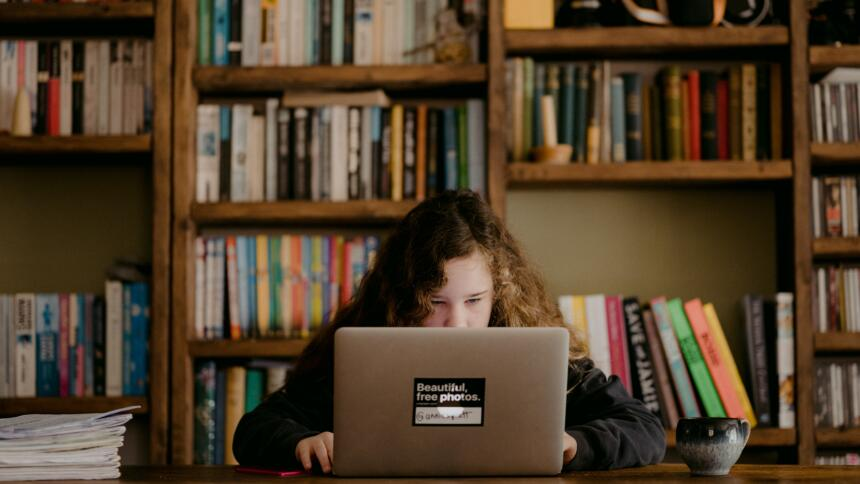 Kind am Laptop vor Bücherwand