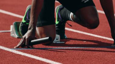 Die Beine eines Sprinters kurz vor dem Start eines Rennens.