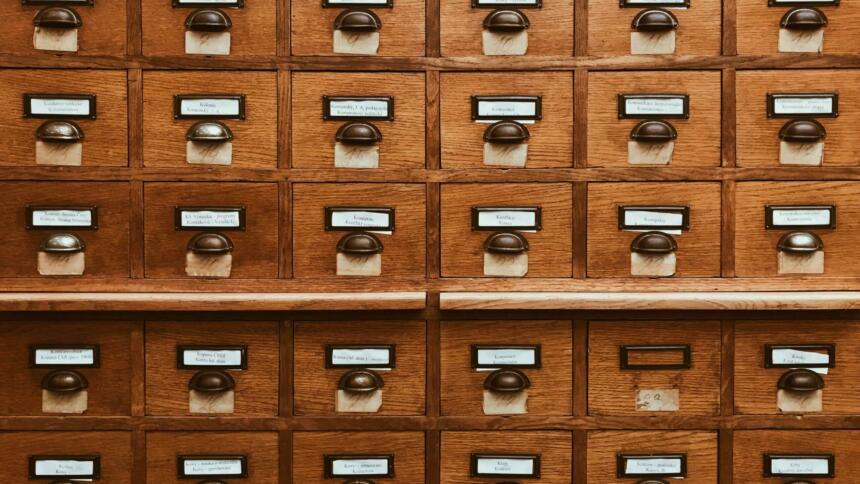 Ein brauner Schrank mit vielen Schubladen, in denen sich vermutlich Karteikarten befinden.
