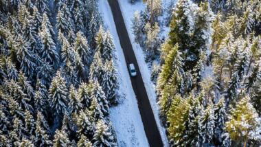 Vogelperspektive: Ein Auto fährt in einem verschneiten Wald auf einer geraden Straße