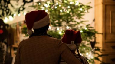 Zwei Personen mit Weihnachtsmützen sitzen vor einem Tannenbaum